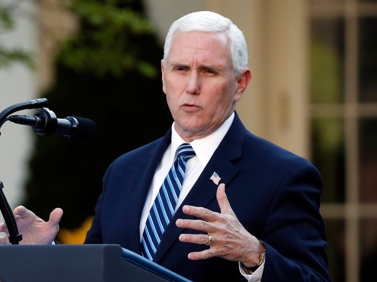 Mike Pence gestures with his hand while speaking into a microphone at a podium.