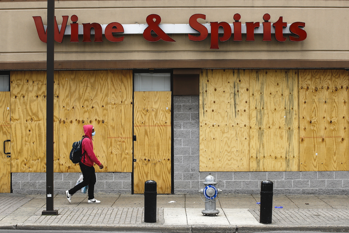 A person wearing a red sweatshirt and a facemask walks down the street past a store called Wine and Spirits, whose windows have been boarded up.