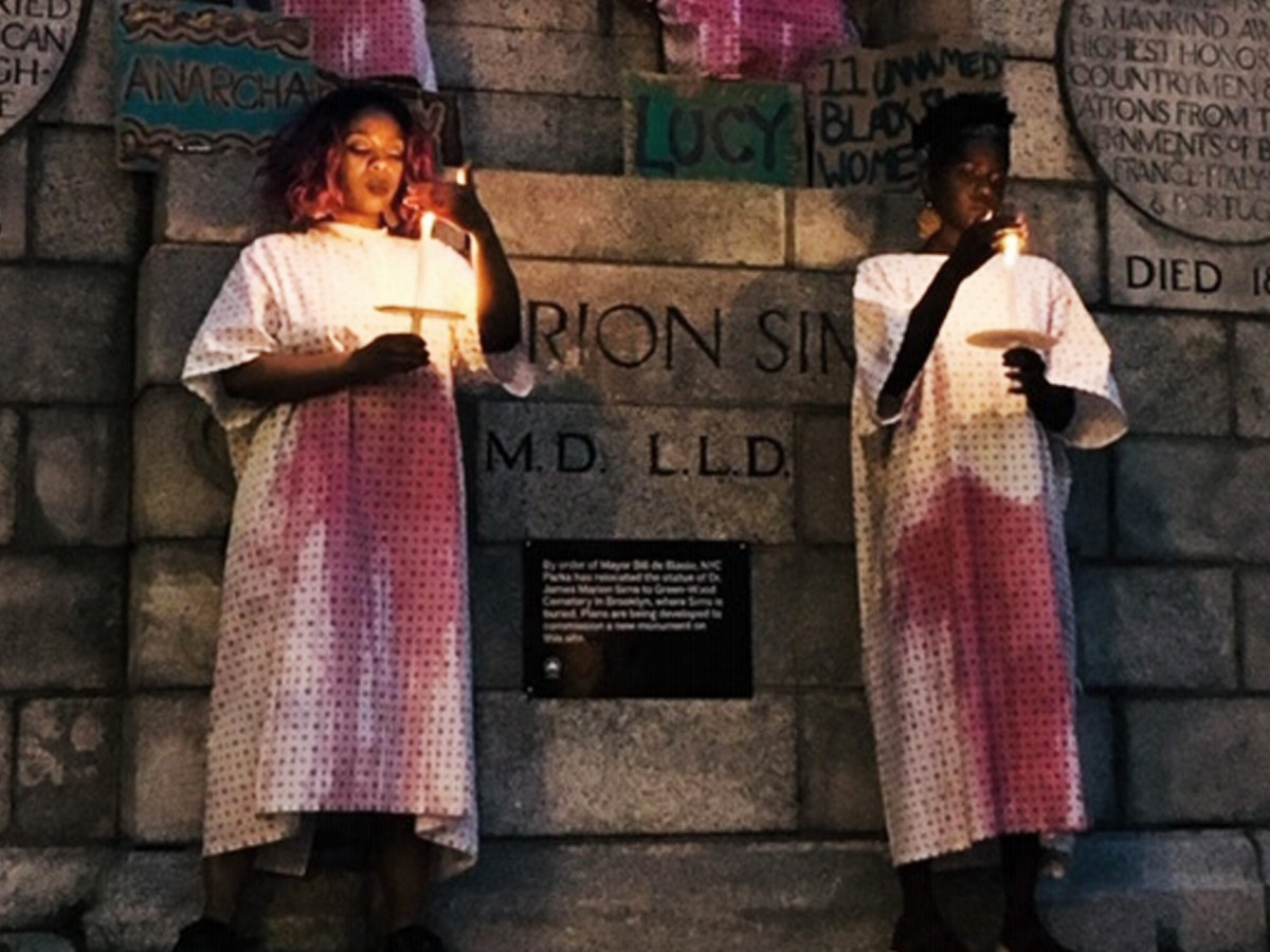 Jewel Cadet and Jamilah Felix are wearing hospital gowns stained with red, each holding a candle in front of a monument carved with Marion Sims' name.