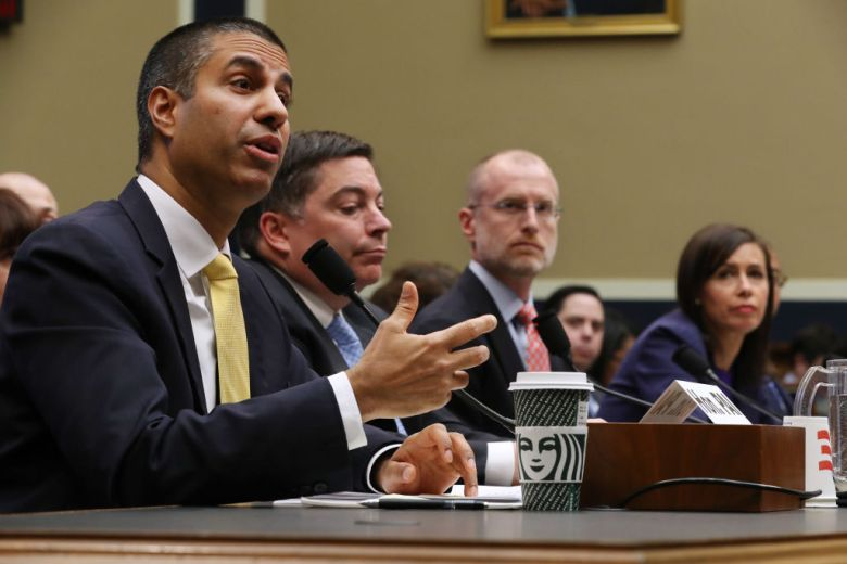 Ajit Pai, wearing a suit and tie, speaks into a microphone during a House meeting.
