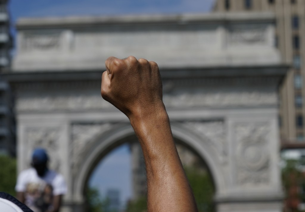 A person with dark brown skin raises their hand in a fist in front of the Washington Square arch.