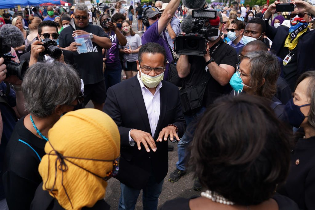 Minnesota State Attorney General Keith Ellison, wearing a mask, speaks in the middle of a large crowd, surrounded by cameras.