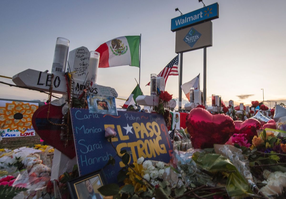 """The sun sets on a memorial left outside an El Paso Walmart. Flowers and balloons crowd around a sign that says """"El Paso Strong."""" A Mexican flag and US flag fly behind the memorial."""