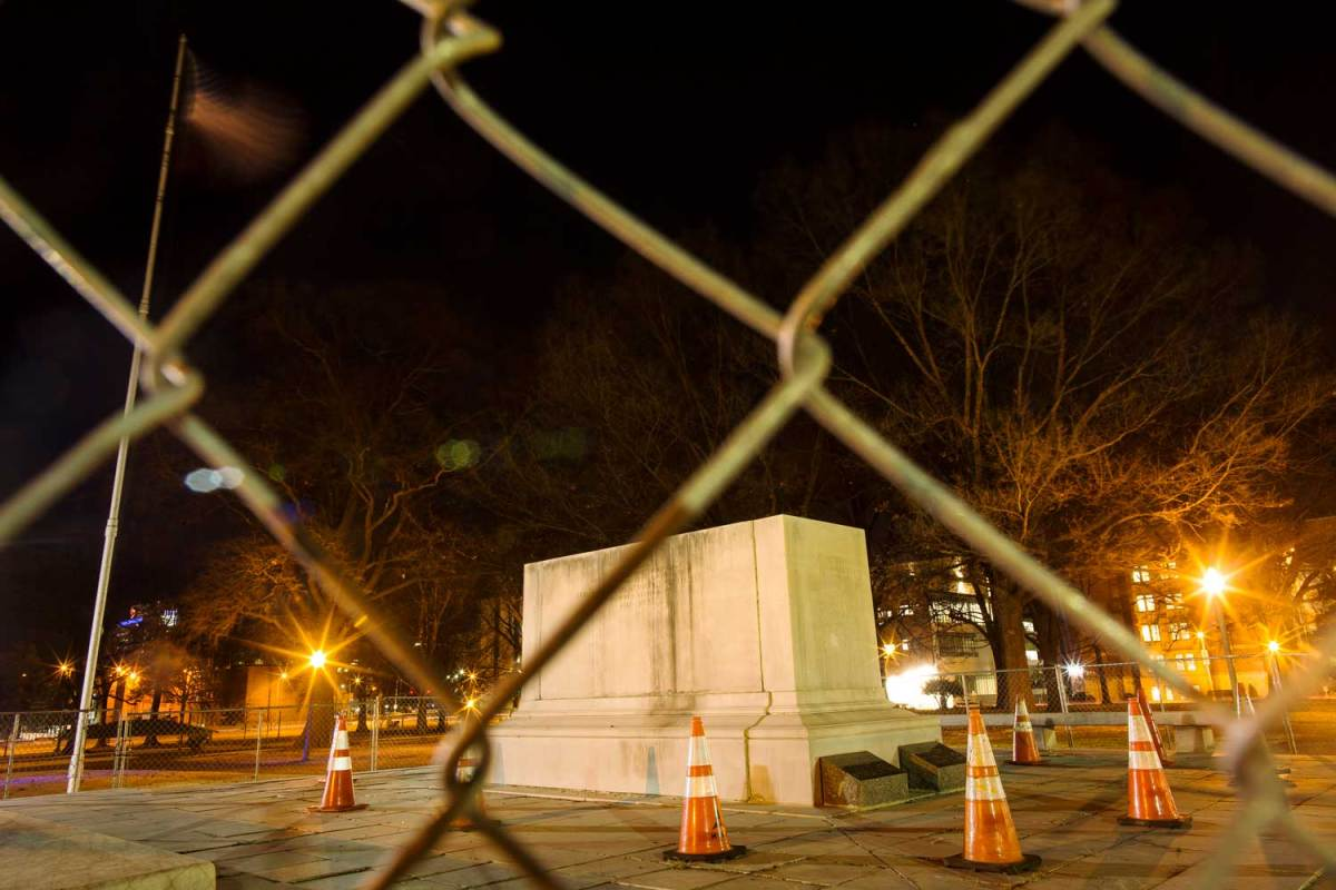 An empty stone pedestal is surrounded by a chain-link fence and orange traffic cones.