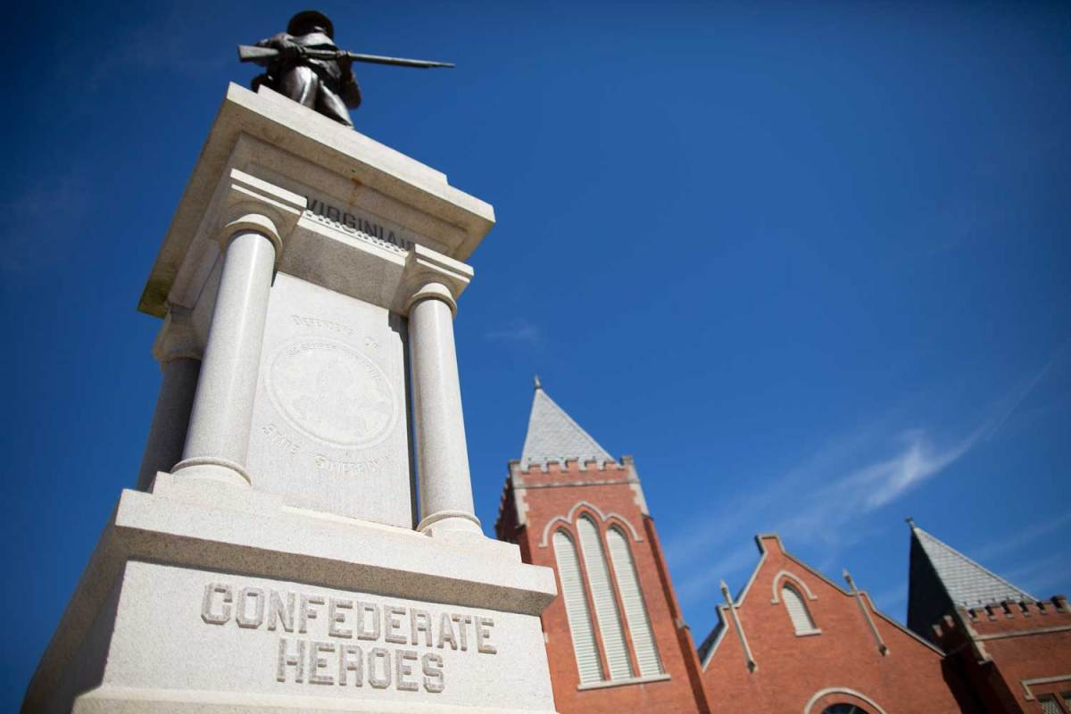 """A monument topped with a statue of a rifle-carrying soldier. The monument's stone base says, """"Confederate Heroes."""""""