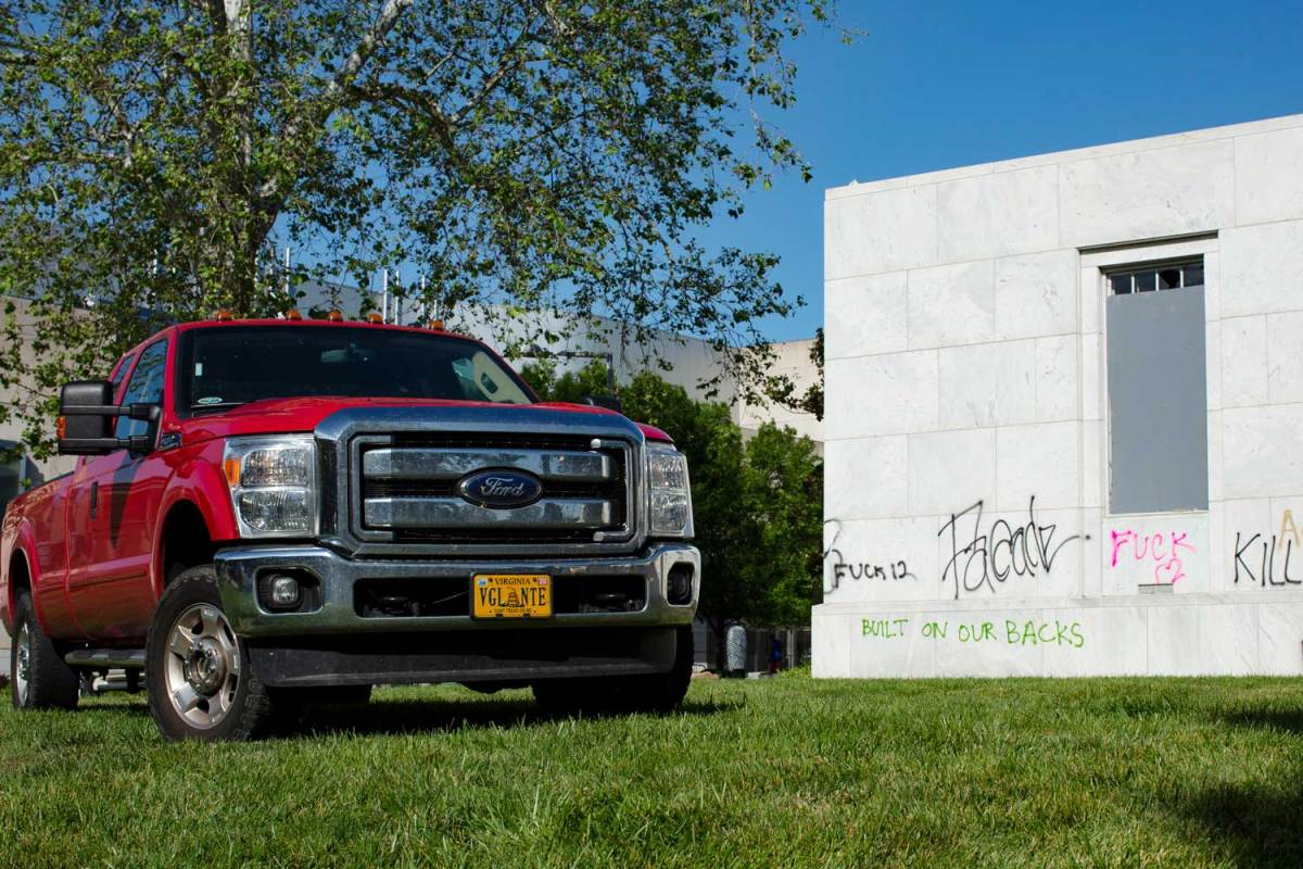 """A red pickup truck with a vanity license plate that reads """"VGL NTE."""" It is parked next to a building tagged with anti-police graffiti."""