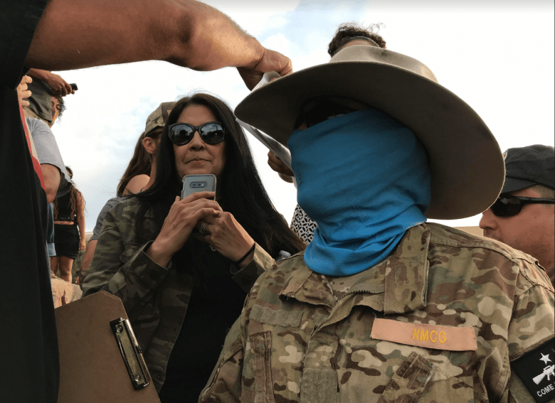Bryce Provance stands in the middle of a crowd. Behind him, a woman films on her phone camera. His face is wrapped in blue fabric, he is wearing a cowboy hat and camo-print fatigues. A name badge on his chest says NMCG (New Mexico Civil Guard).