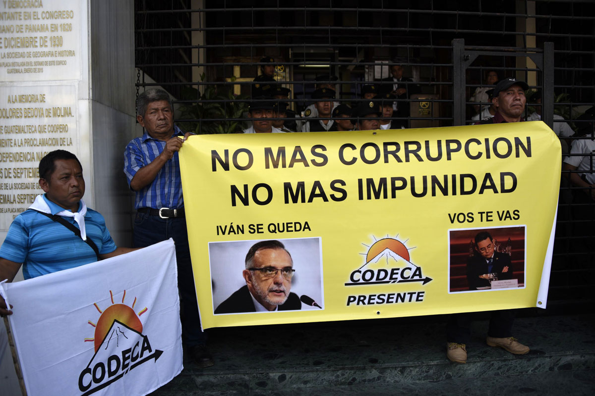 """Several men hold a banner, which features photos of Iván Velásquez and Jimmy Morales. The banner's top says: """"No mas corrupcion, no mas impunidad."""""""