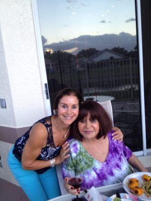 Carrie Morris poses with her mother, Anita Lymber, at an outdoor dining table.
