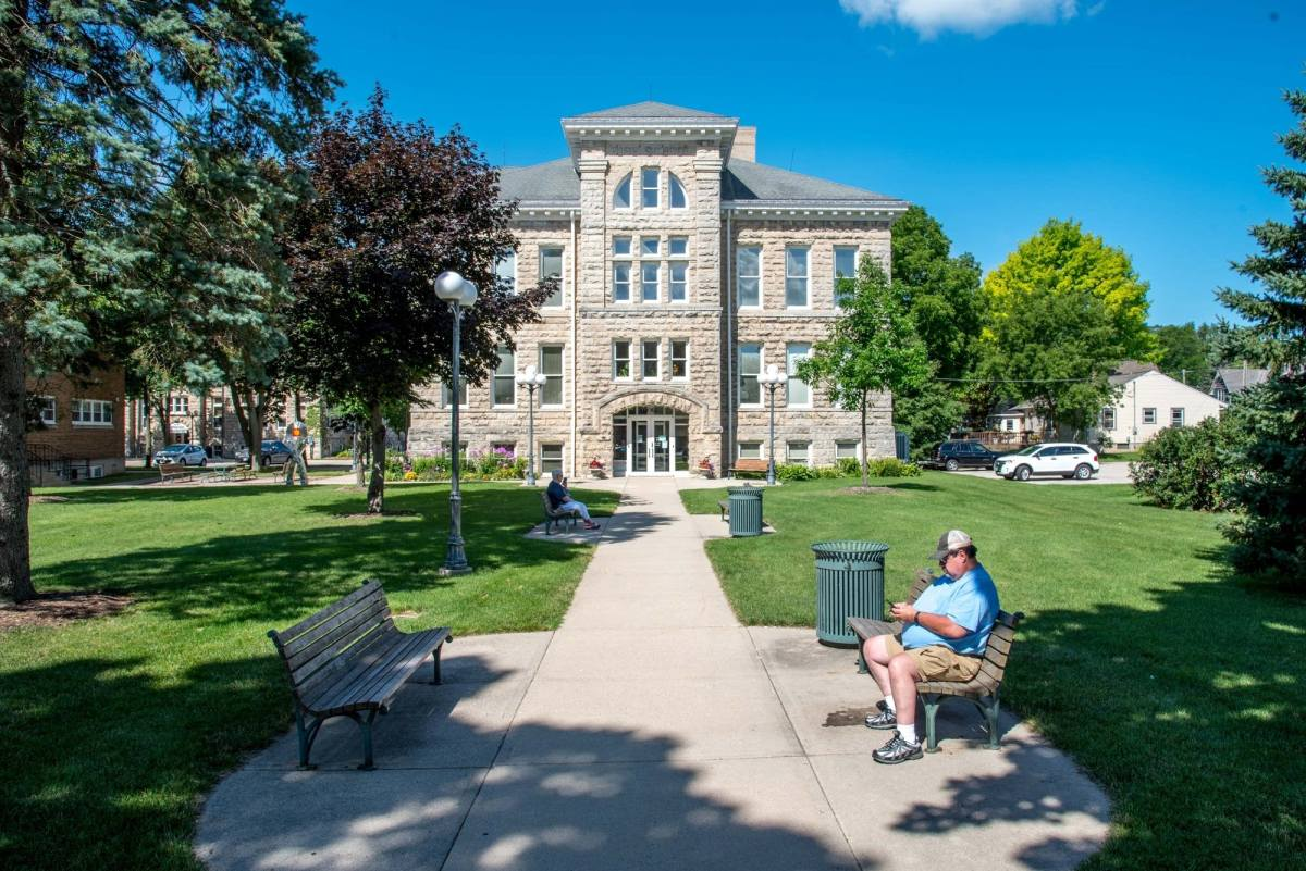 Cedarburg's City Hall faces a grassy square with park benches.