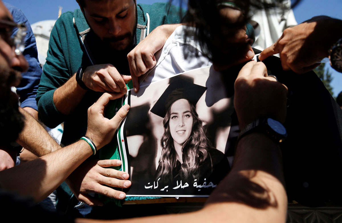 The hands of several people hold up a large photograph of Halla Barakat. In the photo, she's wearing a graduation cap and gown.