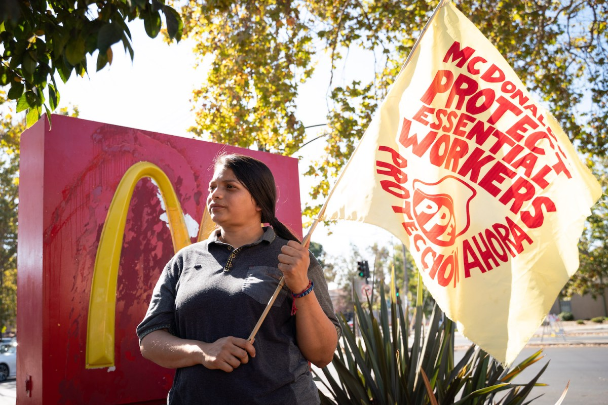 """Angely Rodriguez stands in front of a McDonald's sign, holding a protest banner. It reads: """"McDonald's, protect essential workers, protección ahora."""""""