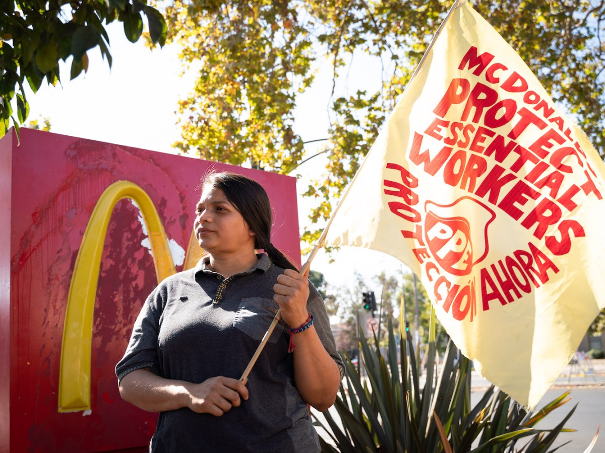 "Angely Rodriguez stands in front of a McDonald's sign, holding a protest banner. It reads: ""McDonald's, protect essential workers, protección ahora."""