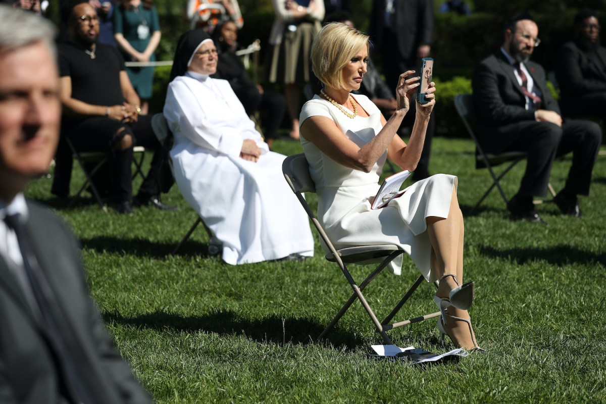 Paula White sits in a folding chair, using her cellphone to take photos. Other attendees sit in chairs spaced several feet apart for social distancing.