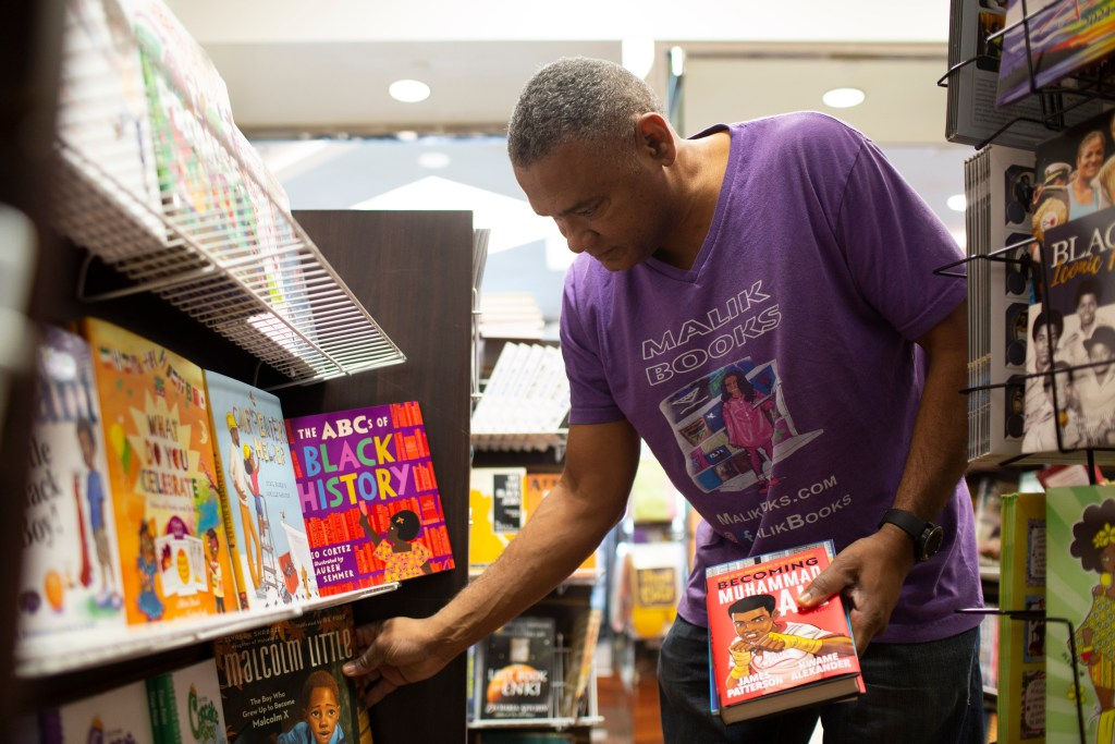 "Malik Muhammad, wearing a store-branded T-shirt, puts away books on a shelf. In his left hand is a book titled, ""Becoming Muhammad Ali."""
