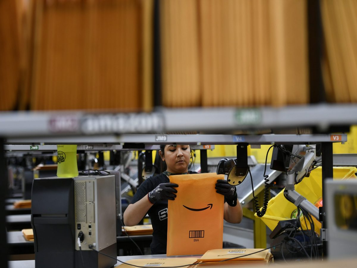 A worker packs items into an Amazon-branded envelope at a warehouse.