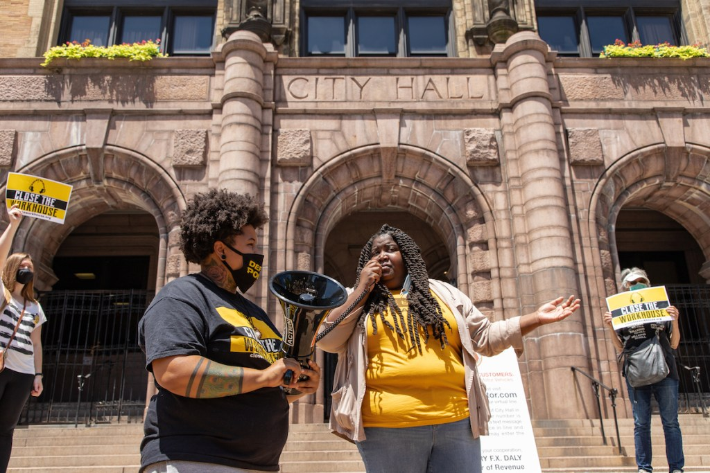 """Kayla Reed speaks into a megaphone held by Jae Shepherd. Behind them, two others hold signs reading, """"Close the Workhouse."""""""