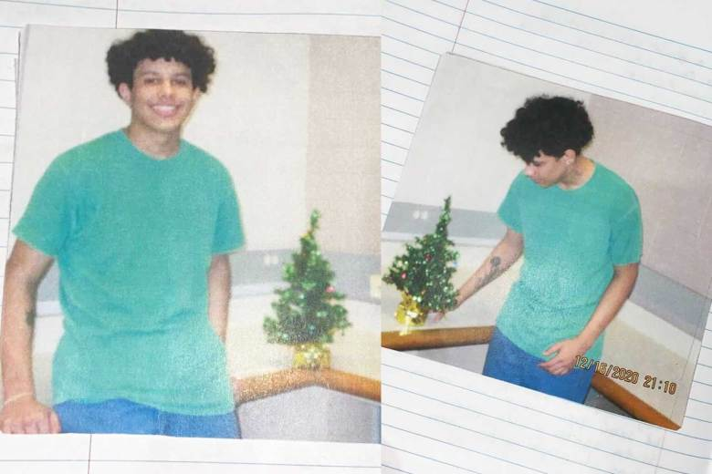 Kaio Bispo stands next to a small tinsel Christmas tree.