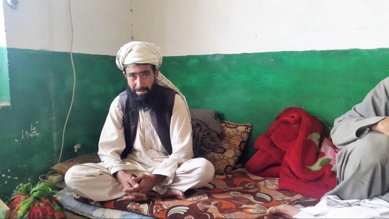 Pasta Khan sits cross-legged on a bed.