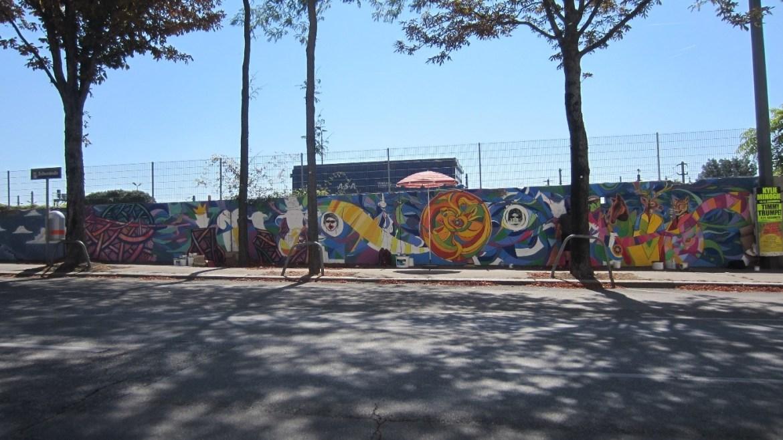 Vista global del mural de Renacho Melgar, con la sombrilla plantada en el medio de la cera