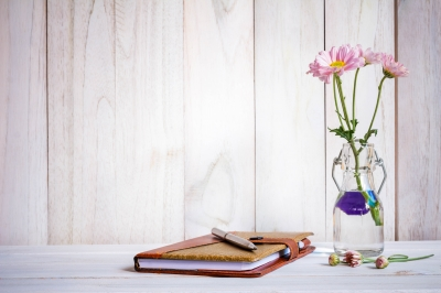 Notebook Or Journal With Pen Of Flowers Arranged On A Neutral White Painted Desk Stock Photo