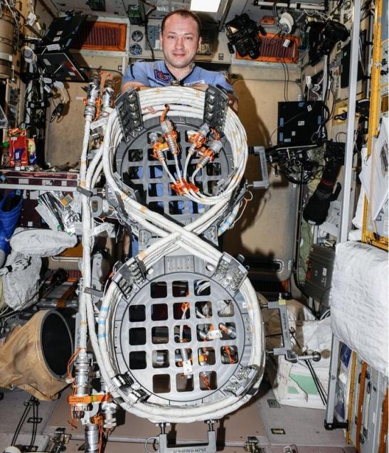 Aleksandr Misurkin présentant les câbles d'alimentation avant leur installation à l'extérieur de la Station (photo NASA)