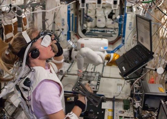 Dans le laboratoire Destiny, l'astronaute Karen Nyberg (Expedition 36) fait de la réalité virtuelle avec le Robonaut 2 pour tester la transmission de commandes à la fois depuis l'espace et le sol.