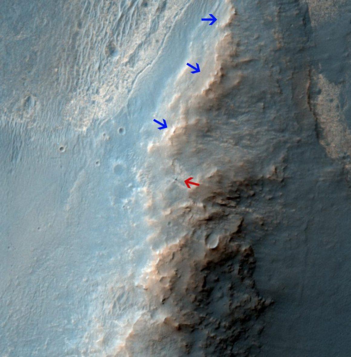 """Image de la caméra HiriSe de Mars Reconnaissance Orbiter de la NASA : vue du Mars Exploration Rover """"Opportunity"""" le 14 février 2014. La flèche rouge montre Opportunity au centre de l'image. Les flèches bleues indiquent les traces laissées par le rover depuis son entrée dans la zone en Octobre 2013 . La scène couvre une parcelle de terrain d'environ 400 mètres de large. Le Nord est vers le haut. (crédit NASA/JPL-Caltech/Univ. of Arizona)"""
