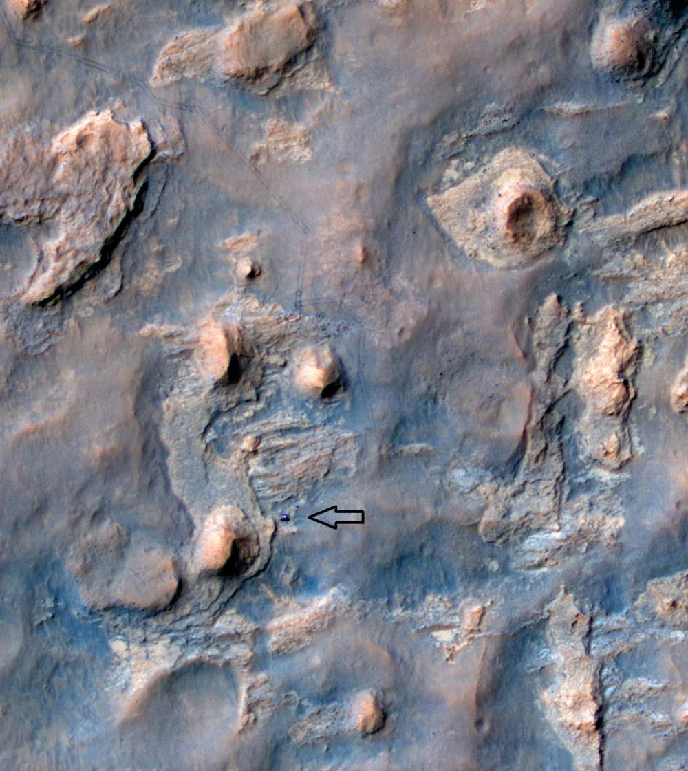 Curiosity est visible [flèche] sur cette photo, en couleur améliorée, prise par la caméra HiRise de Mars Reconnaissance Observer en orbite autour de Mars (source NASA/JPL)