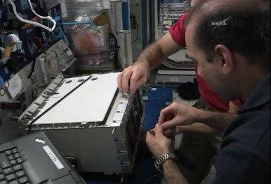Rick Mastracchio et Steve Swanson en train d'installer un nouveau circuit intérieur d'un multiplexeur-démultiplexeur MDM de rechange à bord de l'ISS en prévision de l'EVA 26 (source NASA TV)
