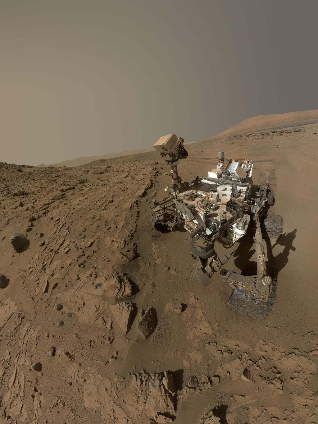 """Curiosity a utilisé l'appareil photo Mahli au boit de son bras en Avril et Mai 2014 pour prendre des dizaines d'images qui ont été combinées dans cet autoportrait. Il est dans la région appelé """"Windjana"""" et on peut y voir le forage et le pré-forage effectués dans la roche (2 ronds gris un peu à gauche du centre de l'image) (Crédit: NASA / JPL-Caltech / MSSS)"""