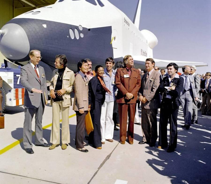 """En 1976, la navette spatiale de la NASA Enterprise sort des installations de fabrication Palmdale et a été accueilli par les responsables de la NASA et les membres de la distribution de la série télévisée 'Star Trek'. De gauche à droite : l'Administrateur de la NASA Dr James D. Fletcher; DeForest Kelley, (Dr """"Bones"""" McCoy dans la série); George Takei (M. Sulu); James Doohan (l'ingénieur en chef Montgomery """"Scotty"""" Scott); Nichelle Nichols (Lt. Uhura); Leonard Nimoy (Spock); le créateur de la série Gene Roddenberry; l'élu à la Chambre des représentants des États-Unis Don Fuqua ; et, Walter Koenig (Enseigne Pavel Chekov). Credit NASA"""