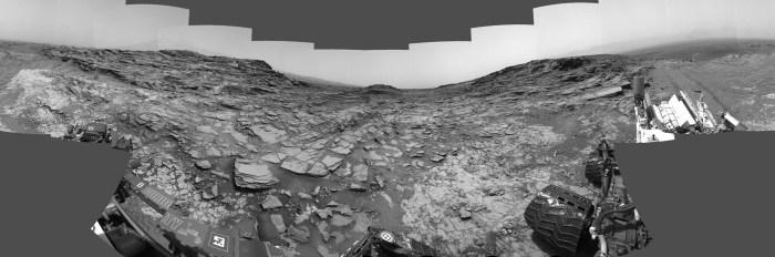 """Ce panorama à 360 ° a été réalisé à partir d'images prises par la caméra de navigation (Navcam) du rover Curiosity de la NASA. Il montre les environs d'un site en bas du Mont Sharp, où le rover a passé son 1000e jour martien (ou Sol). Le Sol 1000 de la mission Curiosity correspondait au 30 mai 2015. Les images composant cette scène ont été prises au Sol 997 ( le 27 mai 2015). Le site est une vallée juste en dessous du """"Marias Pass"""" (sorte de petit col) en bas du mont Sharp."""