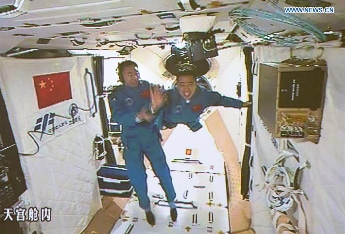 Capture d'écran du 1910/2016 de l'image au Centre de contrôle aérospatial de Pékin montrant les deux astronautes chinois Jing Haipeng (à gauche) et Chen Dong -àdroite) dans le laboratoire spatial Tiangong-2. (credit Xinhua / Ju Zhenhua)