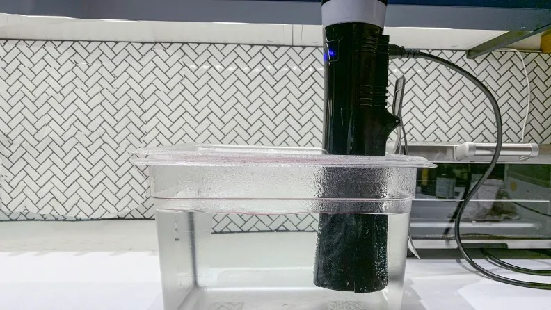 A sous vide immersion circulator attached to the side of a plastic tub that's been partially filled with water.