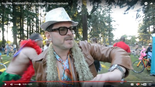 Stephen Upchurch checks his watch before the World Naked Bike Ride at Mt. Scott Park in Portland. Video frame grab by Reviewer TV. Click the pic for the video.