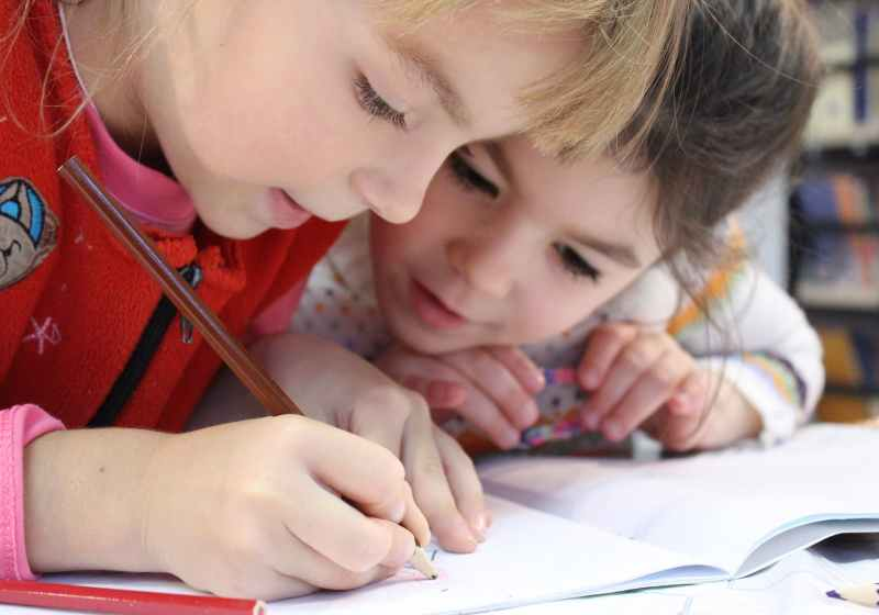 two girls are hunched over a workbook and one is drawing with a colored pencil