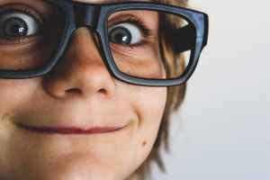 close up of a little kid with oversized reading glasses on