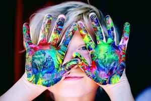 a kids hands are painted with a colorful graphic and they are covering his face but you can see part of his mouth and one eye