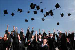 School graduates are throwing their caps up while wearing graduation gowns.