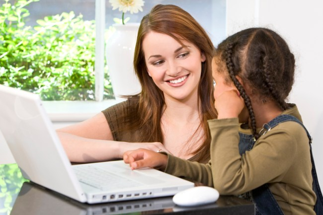 A beautiful young mother and her mixed race young daughter using a laptop computer at home in the kitchen.