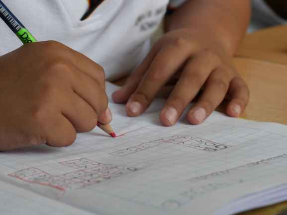 A kid is using a graph paper notebook to work on a project or homework.