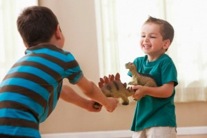 West New York, New Jersey, USA Caucasian boys fighting over dinosaurs Image by © KidStock/Blend Images/Corbis
