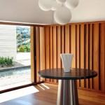 El generoso vestíbulo de entrada tiene como centro una mesa con tapa de mármol sobre una base de acero inoxidable. La altura del recinto es ideal para lucir un colgante de esferas de vidrio opalizado.