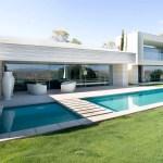 Una pasarela sobre la piscina permite caminar del jardín a la sala, separada de las habitaciones por un volumen intermedio de áreas comunes y servicios.