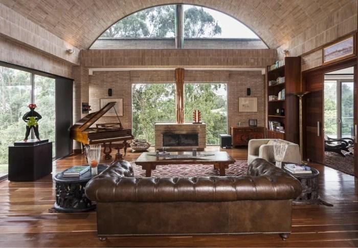 Una ventana enmarca la chimenea con hogar de piedra y buitrón de cobre. Una puerta corredera lateral comunica el estudio con la habitación principal.