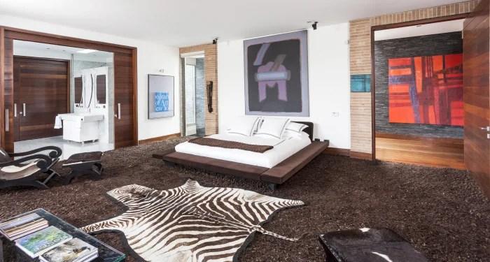 La calidez de un tapete de lana natural da un aire acogedor a la alcoba principal, separada del baño por medio de una puerta corredera.