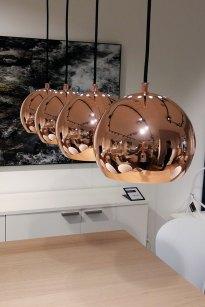 Ball Luminaria esférica de techo en metal con acabado cobrizo. Una propuesta súper de moda. Tiene 18 cm de diámetro y pesa un kilo. También se vende cromada. Aquí se utilizaron cuatro esferas y se colocaron en línea para iluminar la mesa de un comedor en toda su longitud. (BoConcept).
