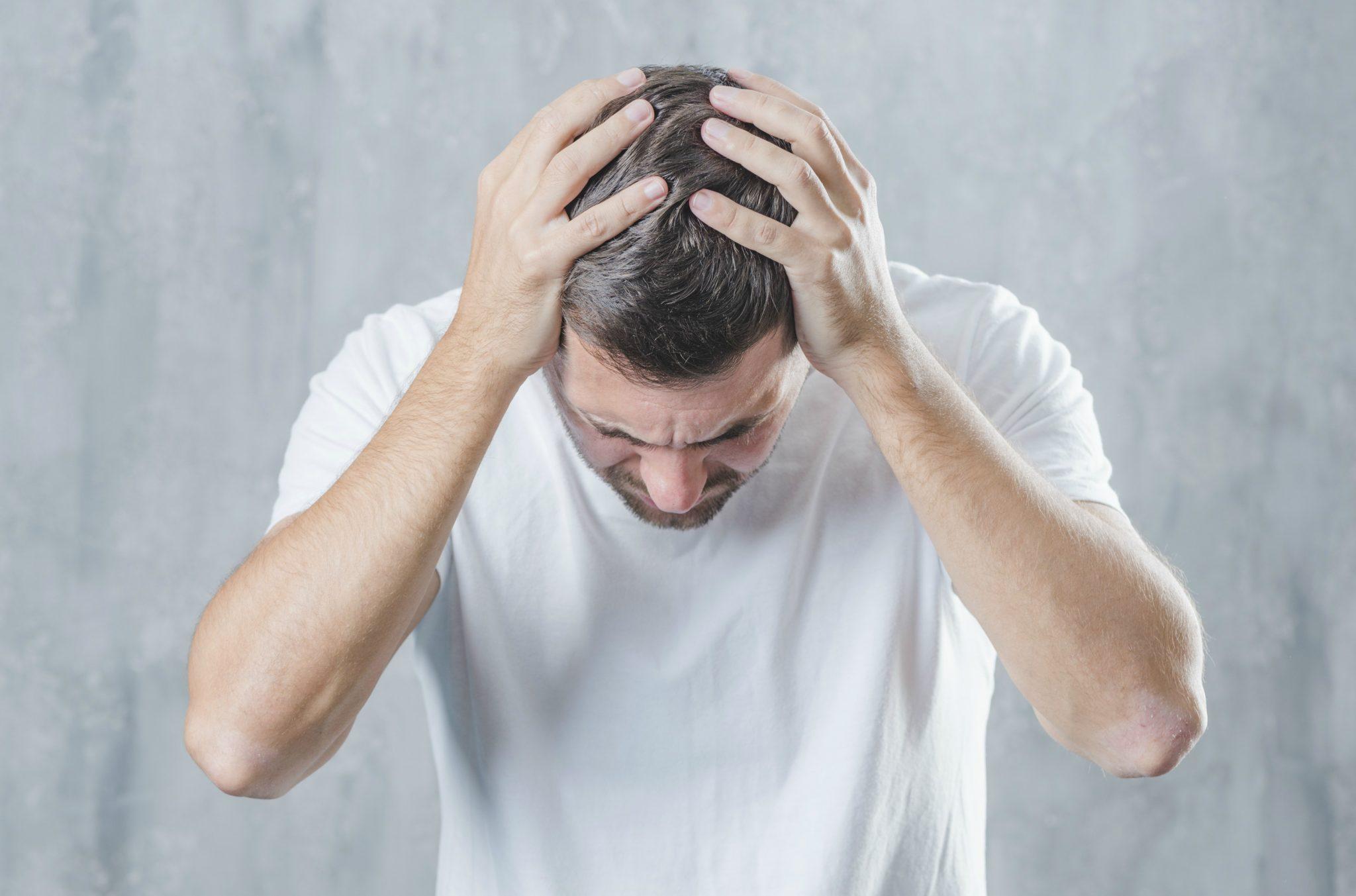Homem sentindo fortes dores de cabeça, sintomas da esquizofrenia