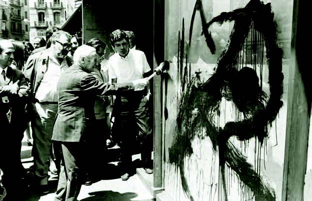 Joan Miró interviene los vidrios de la planta baja del Colegio Oficial de Arquitectos de Cataluña el día de la inauguración de su muestra Miró otro.
